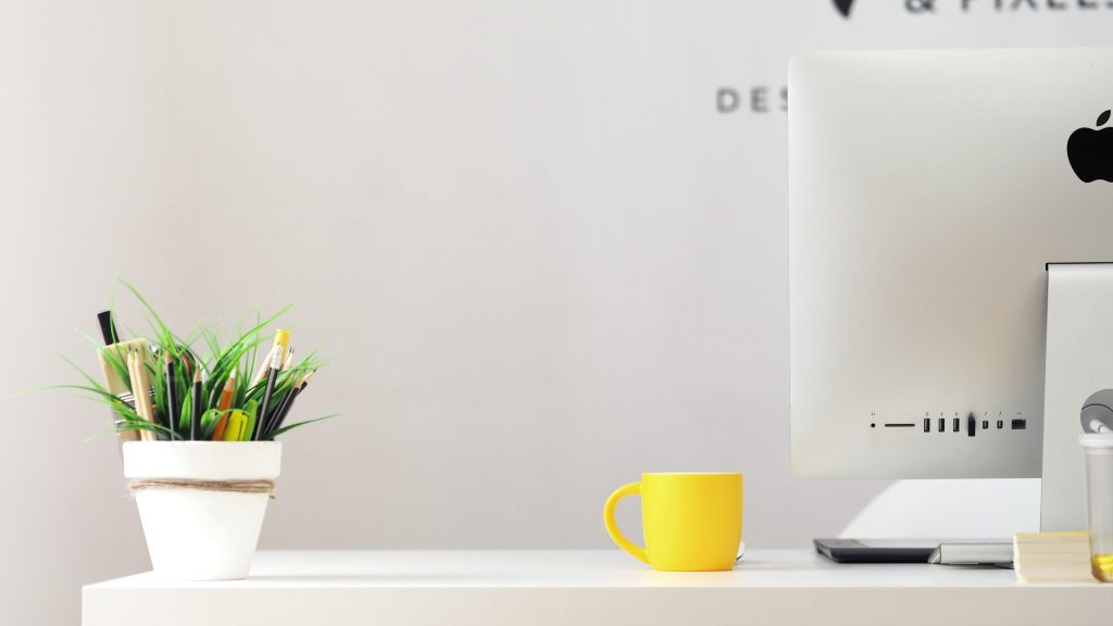 yellow ceramic mug beside gray aluminum iMac
